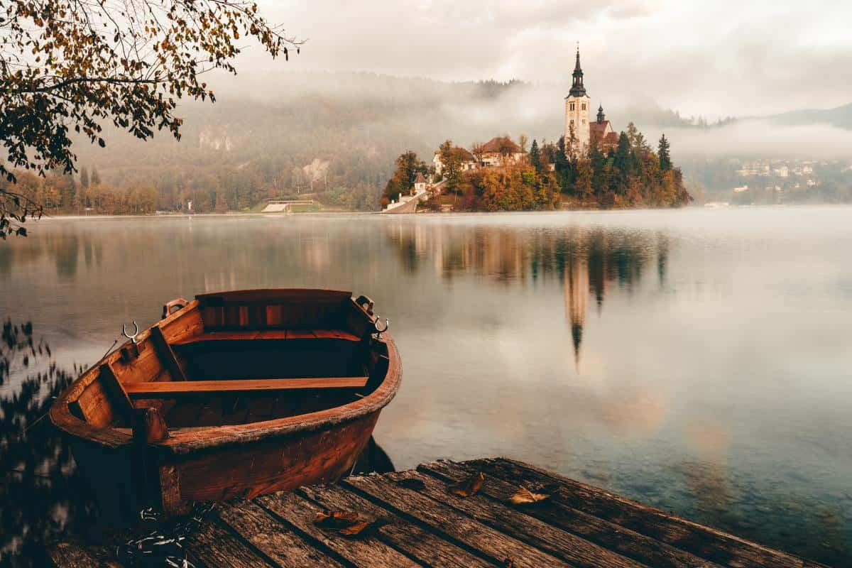 A boat on the shores of Lake Bled with the church in the distance