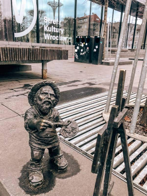 A statue of a gnome painting in Wroclaw, Poland