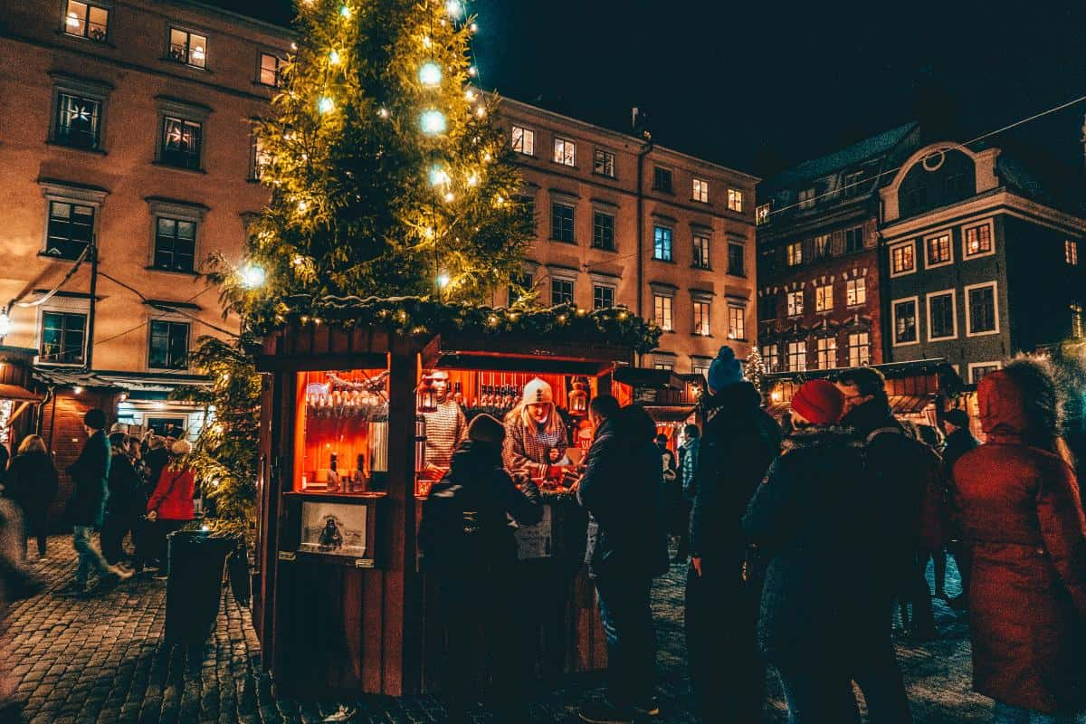A lady selling drinks from a christmas market stall below a christmas tree in stockholm. Sweden