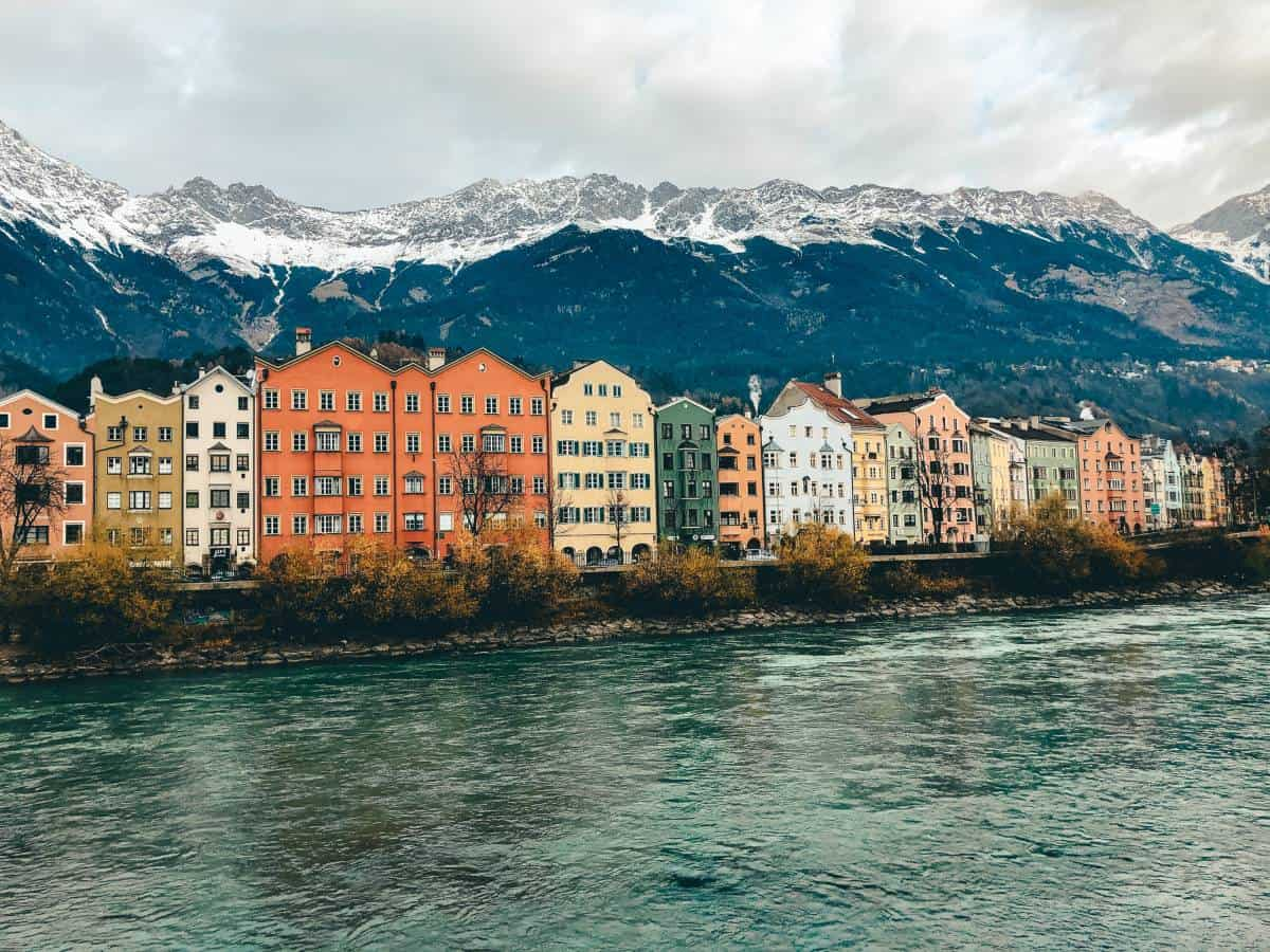 The colourful houses in front of the snow capped Austrian Alps