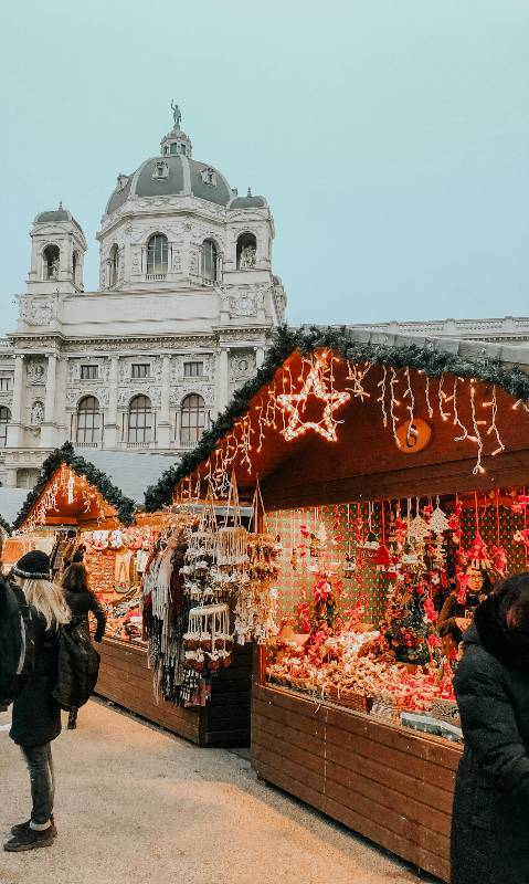 A Christmas market in front of a historic building in Vienna