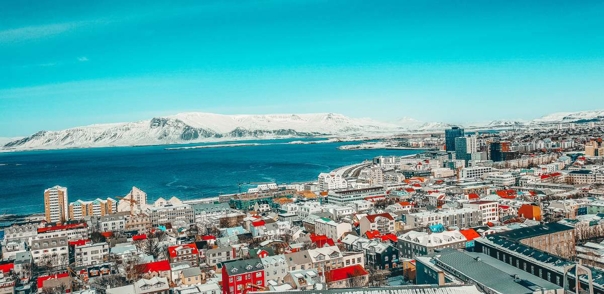 A view over the colourful city of Reykjavik with the ocean and snow covered mountains in the background.