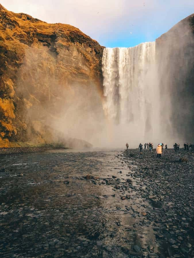 Travellers observing the Skogafoss Waterfall in Iceland