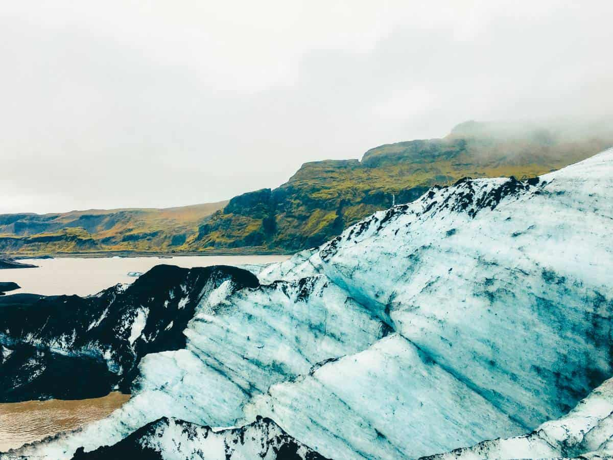 An image Sólheimajökull Glacier in font of a green cliff in Iceland