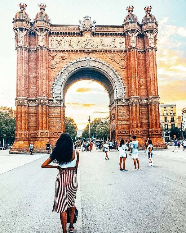 Girl in a strippy skirt standing in front of an old spannish arch