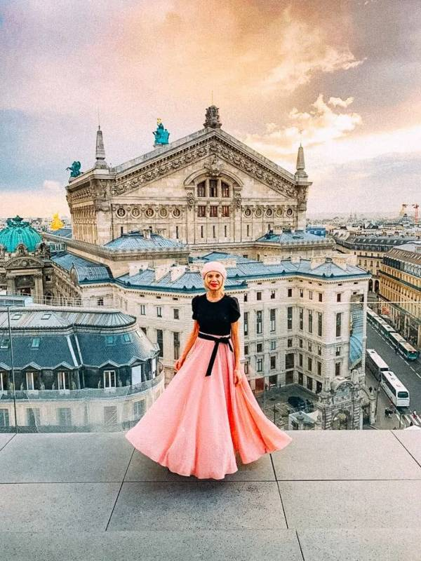 Lady in a pink skirt in front of a Paris building