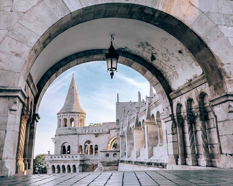 An arch way leading to a white church