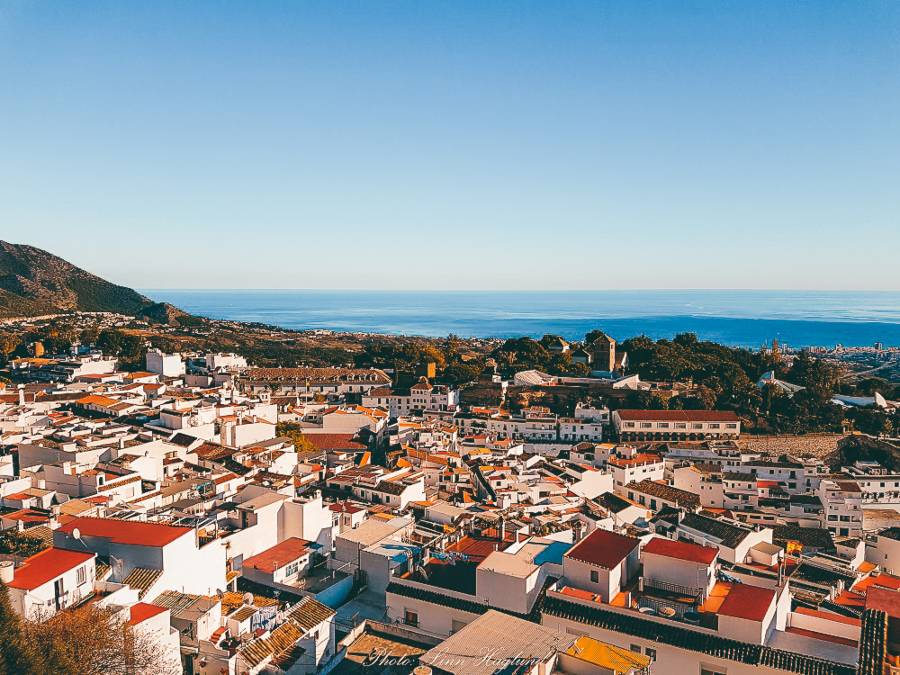 White houses with coloured roofs looking over the ocean