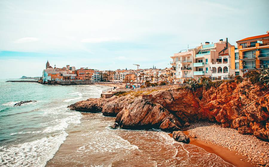 Coloured houses lining a rocky beach in spain