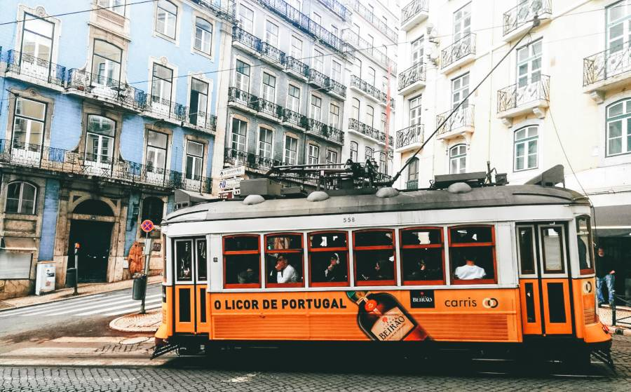 A yellow tram in an old city