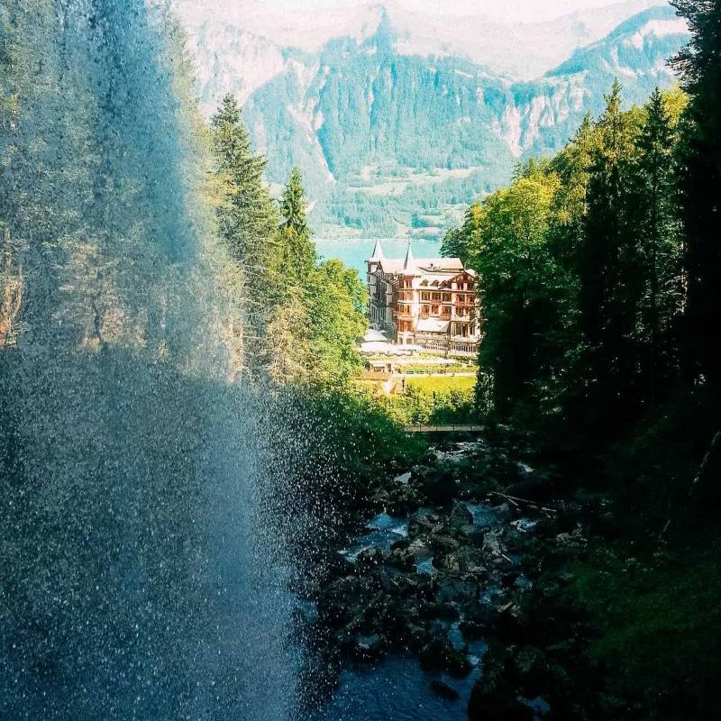 A waterfall with a mansion over looking a lake with mountains behind the lake.