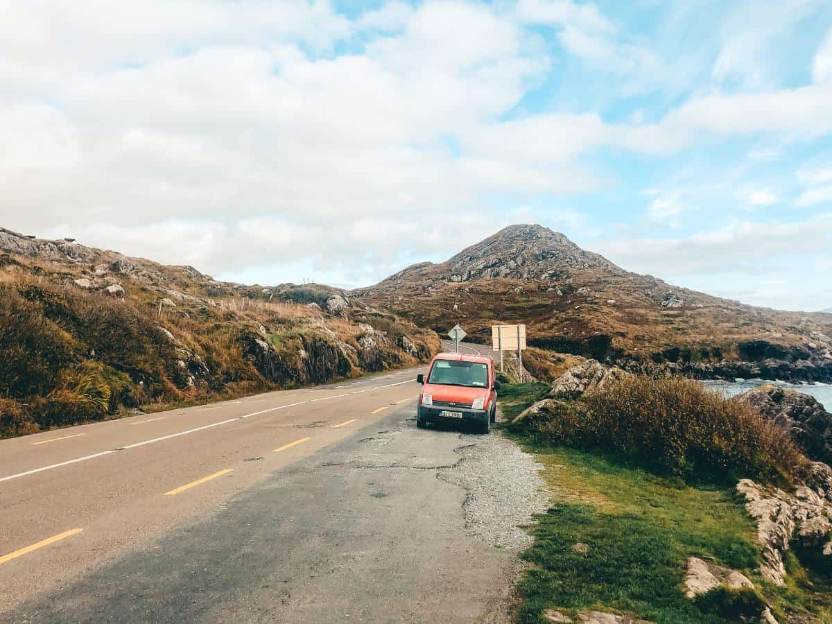A small red van pulled over in layby with mountains behind and coast on the side