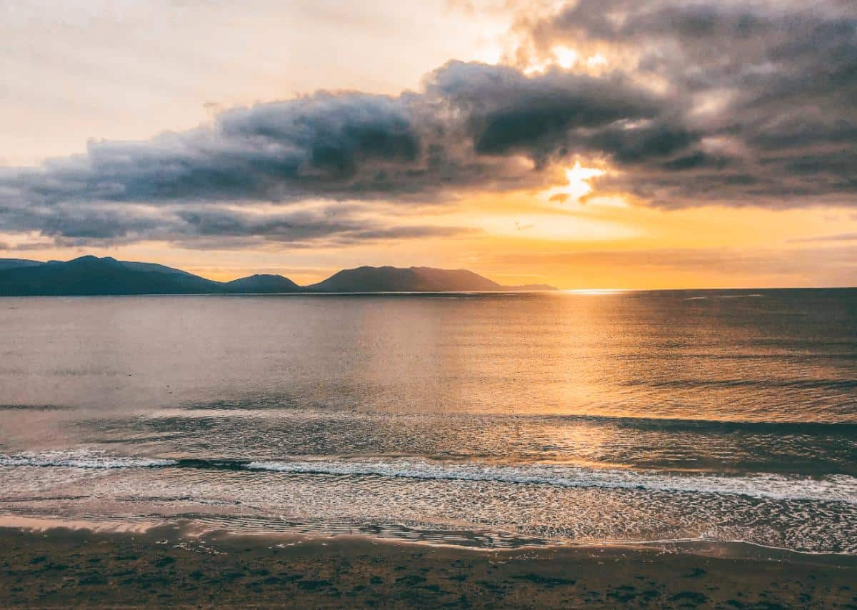 The sunsetting over the mountains on an Irish beach