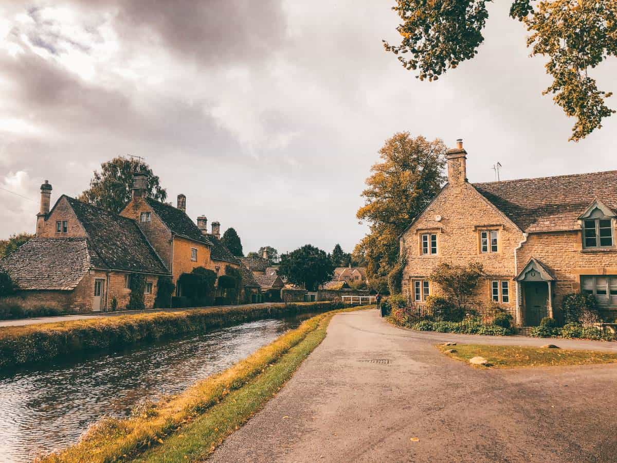 Honeystone cottages on the banks of a river in the Cotswolds