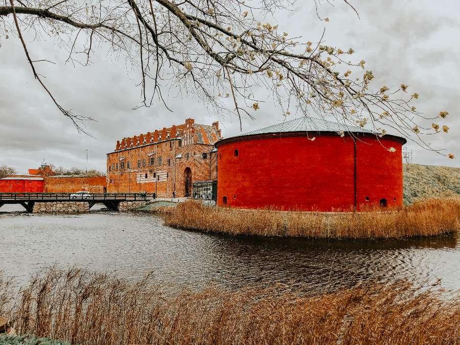 Red circular building next a brick building across the river