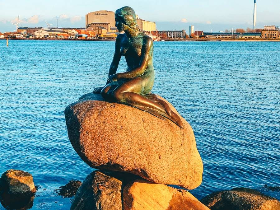 A mermaid statue sitting on a rock in the water