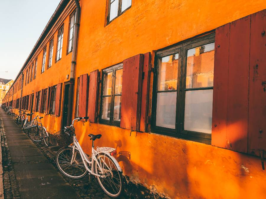 Bright orange double story houses with bikes parked out the front