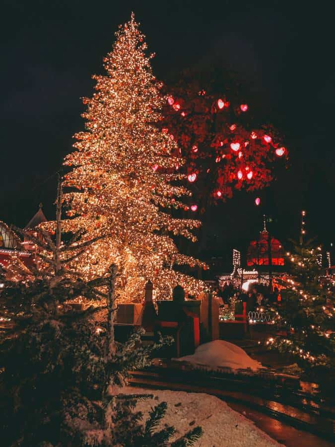 A brightly lit Christmas tree with a miniature train going around the bottom.