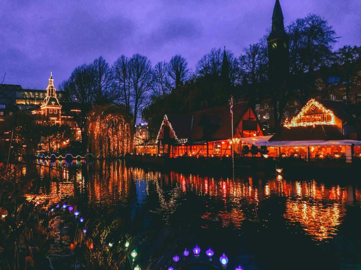 Restaurants lining the lake at Tivoli Gardens at night covered in lights in Copenhagen