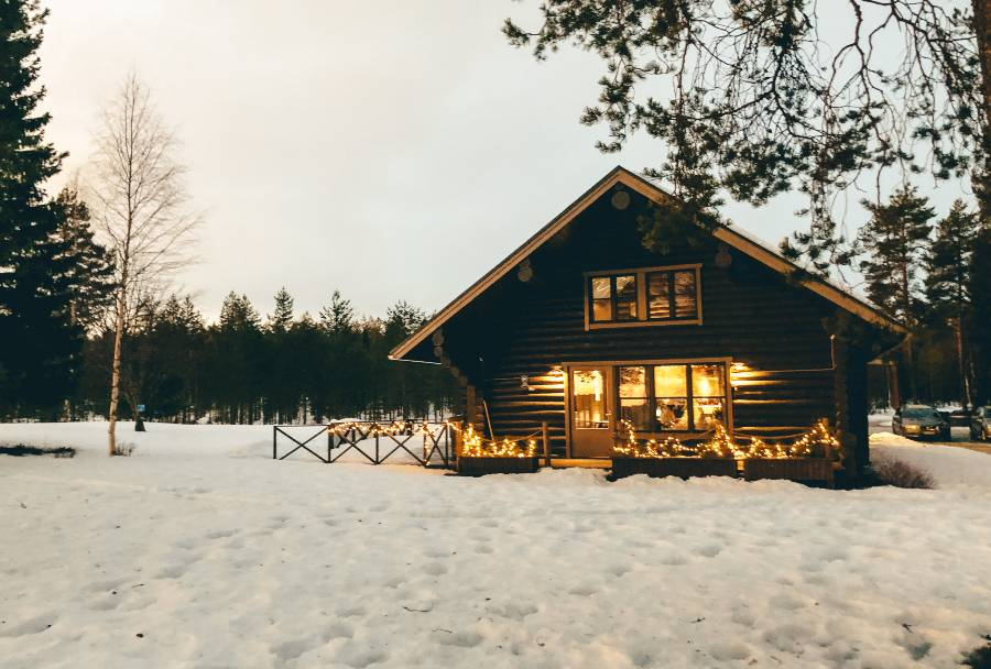 A wooden hut with sun reflecting in the windows surrounded by snow
