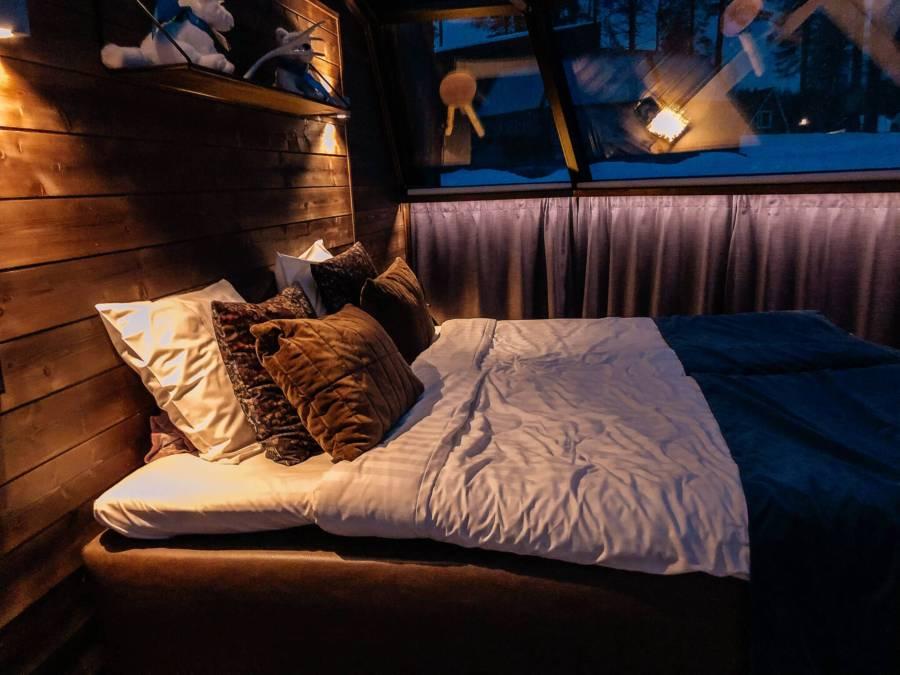 A bed inside a glass igloo with a wooden wall and arctic décor