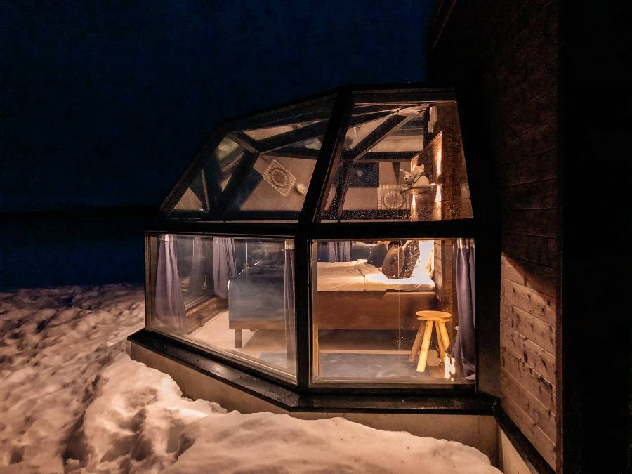 A glass igloo at night time with the light on inside surrounded by snow