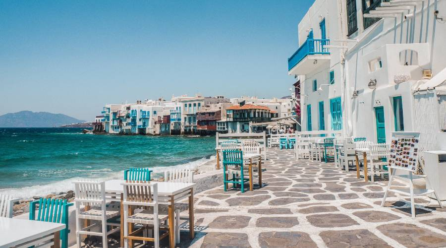 White greek buildings with blue trimmings on the buildings with chairs and tables on the edge of the ocean
