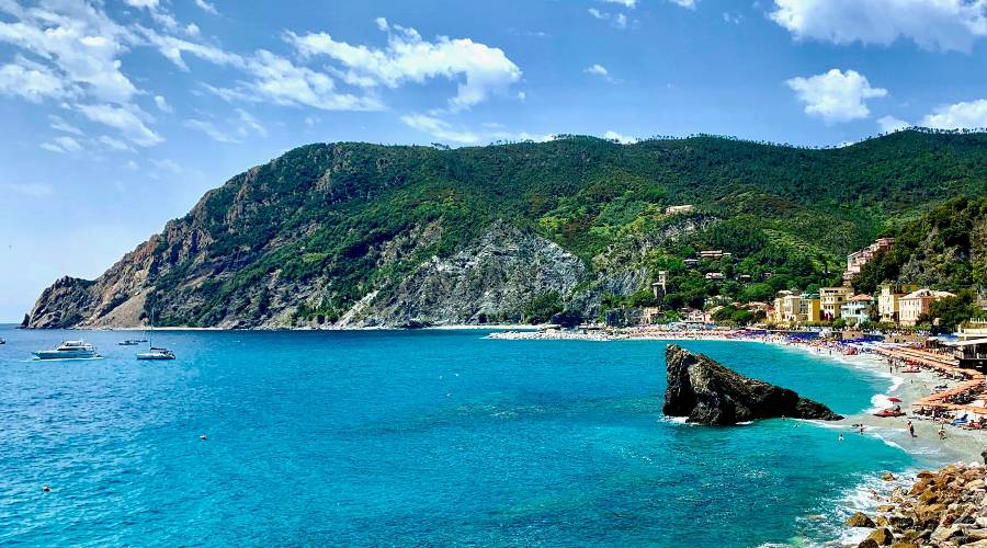 A half moon beach at the bottom of a hills in Cinque terre Italy