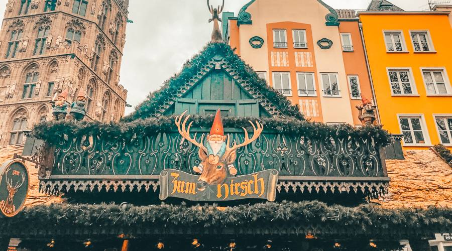 A wooden christmas market stall in front of colourful buildings