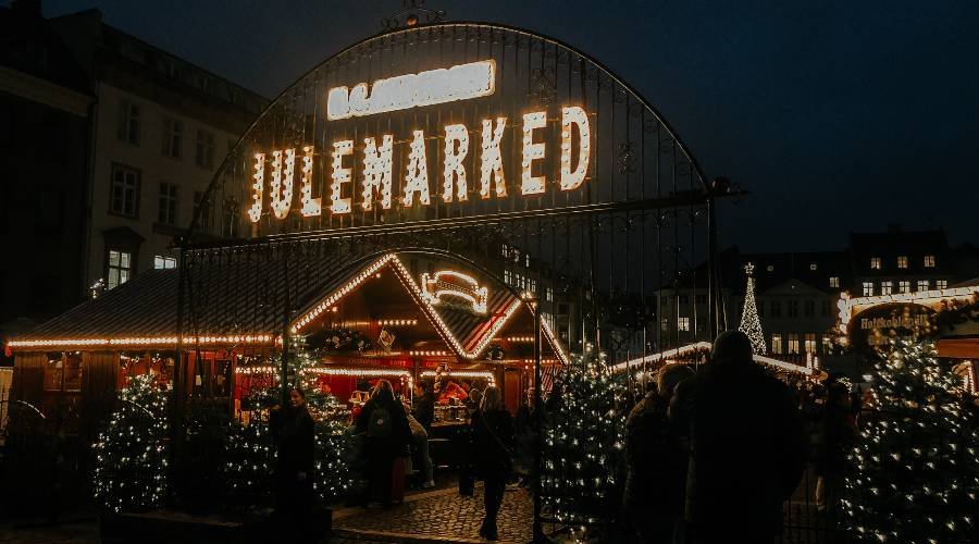 A sign reading Julemarked lit up at night time with Christmas Markets in the background