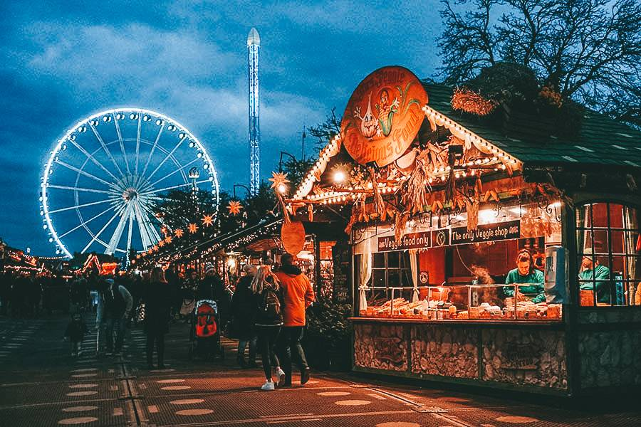 A ferries wheel light up at night time with wooden Christmas markets in the foreground