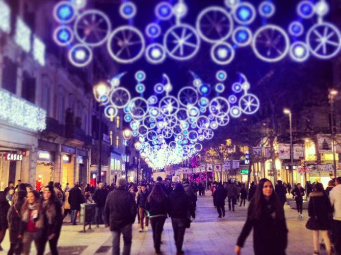 Christmas light decorations above a busy street