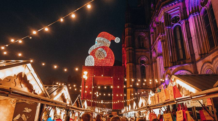 A giant santa sitting on top of a large chair in the middle of Christmas markets in Manchester