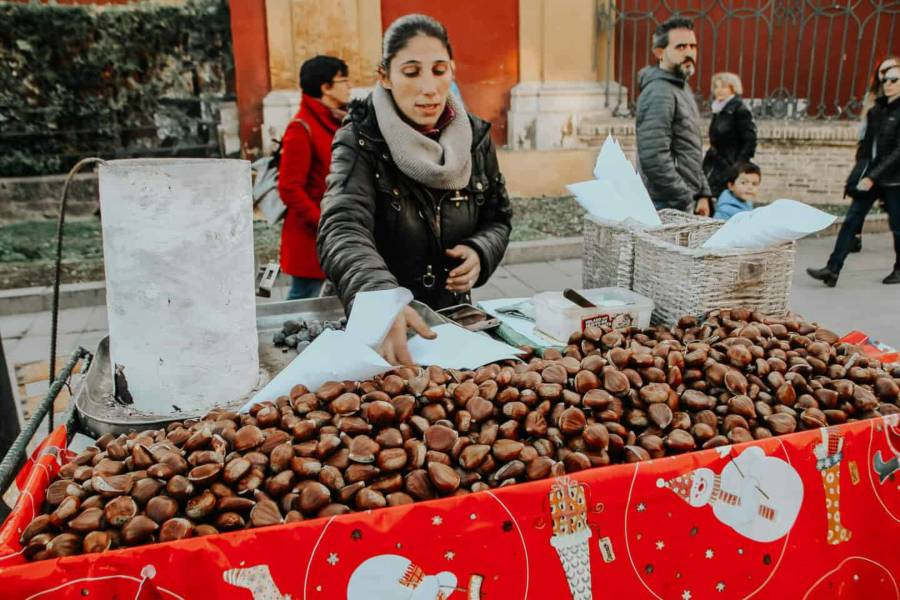 A lady selling roasted chestnuts at Christmas markets in Seville