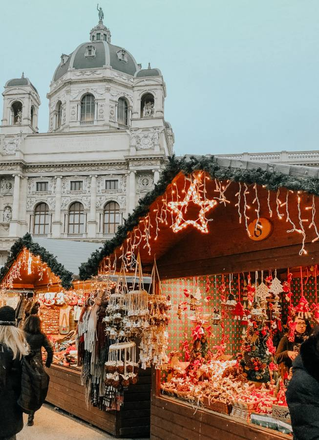 Christmas market stall in front of an old white building with a green dome on top