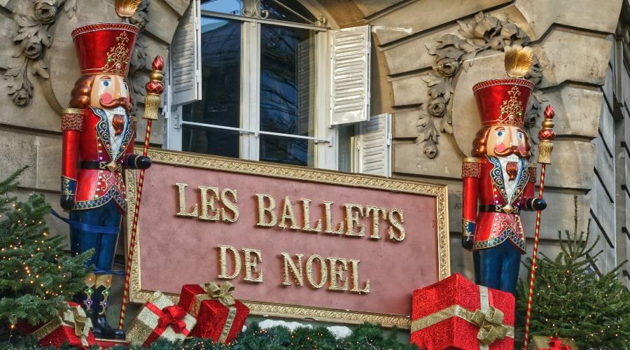 Nutcrackers standing next to a sign reading Les Ballets De Noel