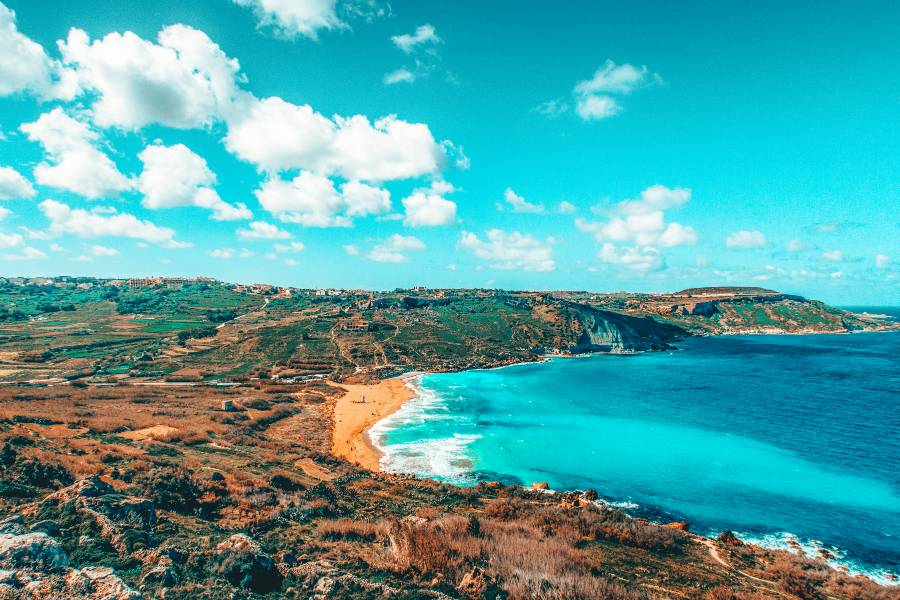 Bright blue sea in a bay surrounded by hills and open land in Gozo, Malta