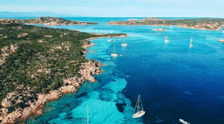A birds eye view of boats floating in the sea surrounding La Maddalena