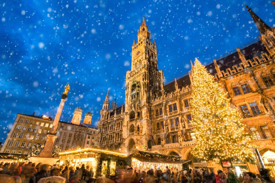 A Christmas market in front of the Town Hall in Munich with snow falling