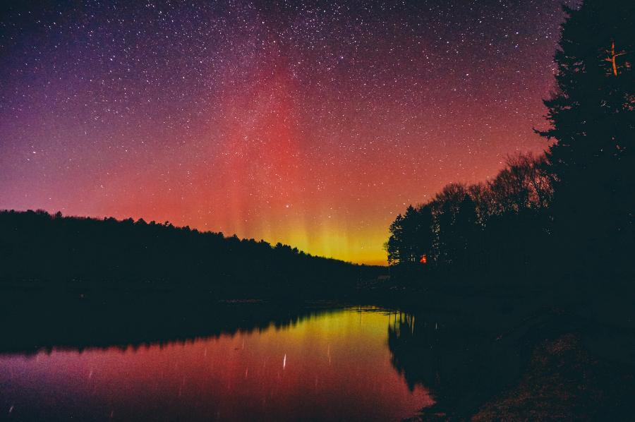 Stars in the night sky filled with pink and yellow northern lights reflecting in a river lined with trees