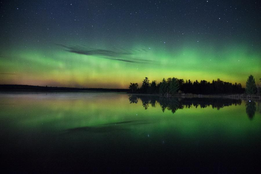 Northern lights in the sky over a lake surrounded by trees