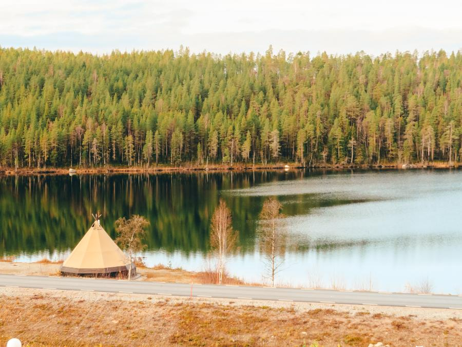 A yurt sitting on the edge of a lake surrounded by trees