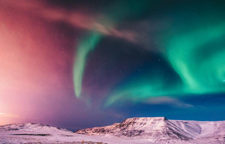 Northern lights in the sky over some snow cap mountains.