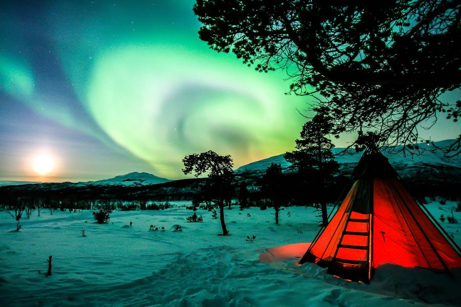 A red tent sitting in the snow under the green northern lights