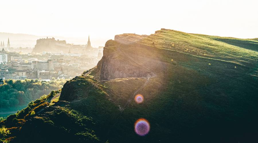 A grassy hill looking over Edinburgh City.