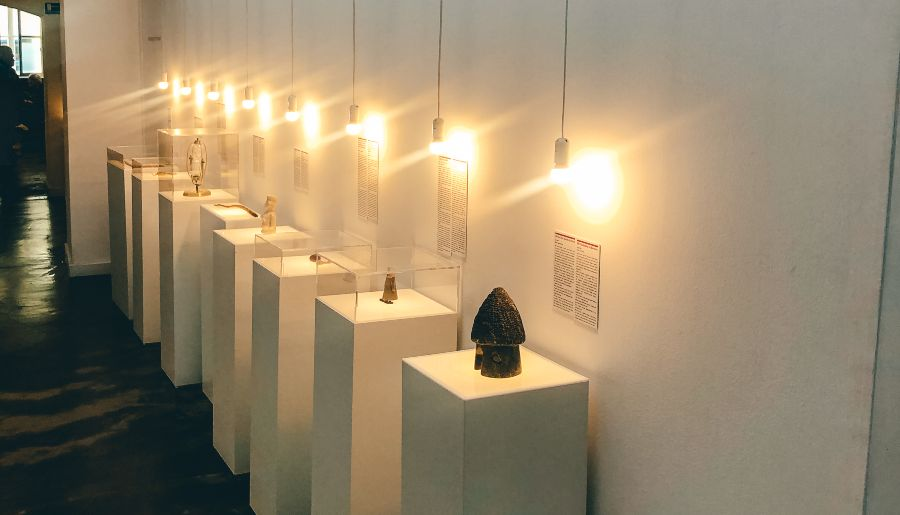 Artifacts sitting on top of white columns under lights at the museum of broken relationships in Zagreb