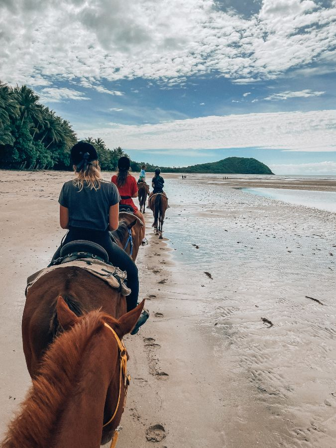 Horses riding along Myall beach in Cape Tribuation