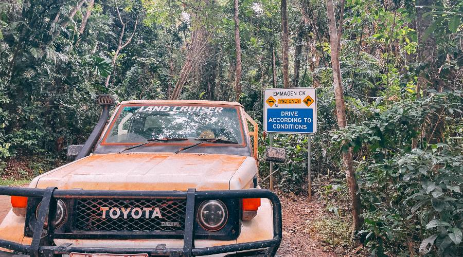 A 4WD covered in red dirt in front of a sign saying 4WD only