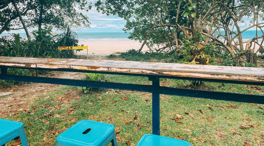 Blue stools under a bench looking out to the ocean