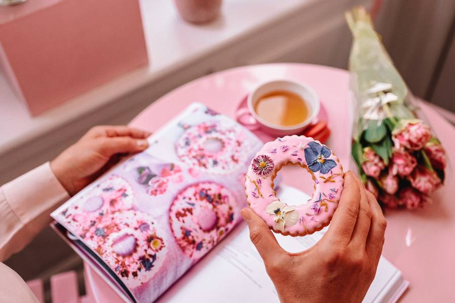 Someone holding a pink biscuit over a table with a book, a cup of tea and flowers